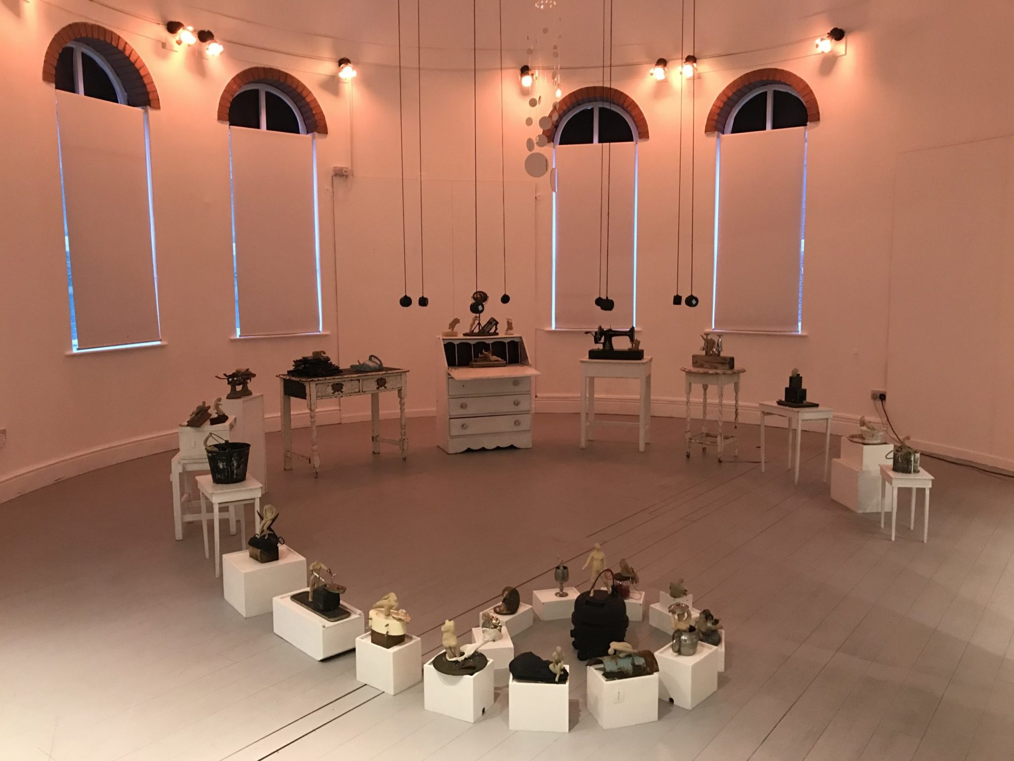 small sculptures on white domestic furniture plinth in a circular gallery with light and sound