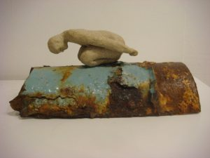 small sculpture of bending figure on pipe