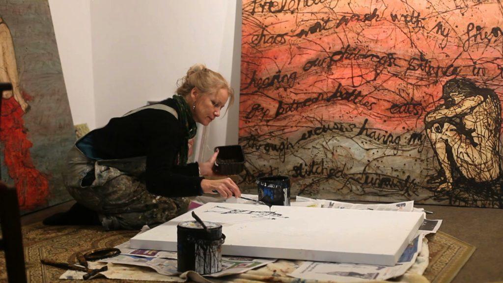artist dripping paint in her studio