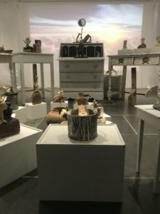 installation of small ceramic figures and domestic objects on furniture with projection of sunrise