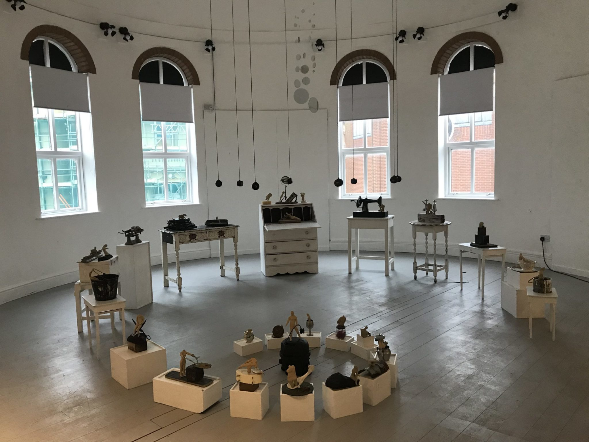 art installation with white furniture poinths and small sculpture at artcore derby