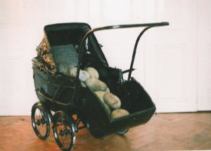 old fashioned pram painted black with granite egg stones and text